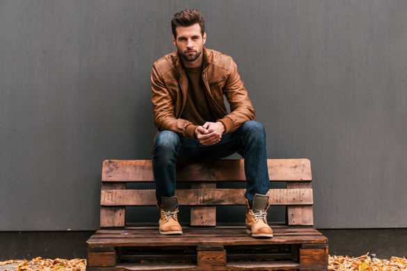 Handsome young Scorpio man sitting on the wooden pallet - Why Scorpio Men Are Not Forthcoming With Their Feelings