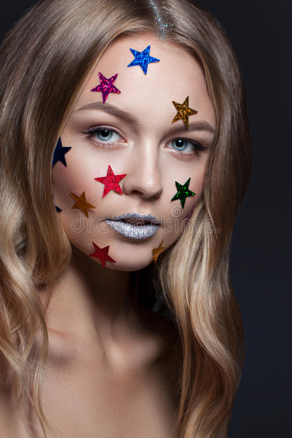 Fashion beauty glamor girl. Multi-colored metallic stars in her hair. Fashion beauty glamor girl. Multi-colored metallic stars in her hair on a light background royalty free stock photography