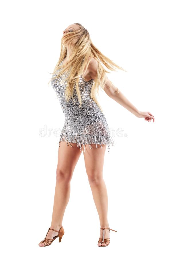 Woman in shiny metallic dress dancing passionately with tousled hair over her face. Full body length portrait isolated on white studio background stock photography